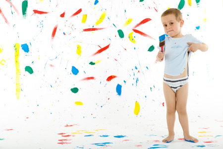 3 year old boy: Adorable 3 year old boy child creatively stains on the wall, floor with colourful paint. Mess of paint on wall, floor and everywhere.