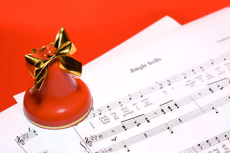 Red-color festive Christmas background: bell standing on notes of christmas song Stock Photo
