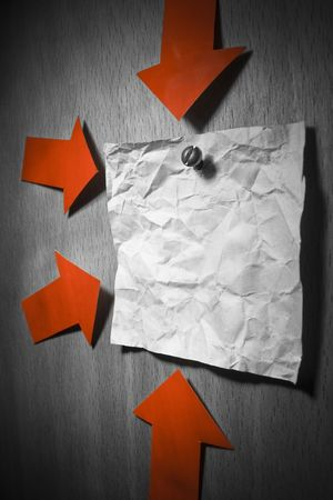 pointed arrows: Business conceptual image. Crumpled office note paper attached to wall by screw and pointed by red arrows