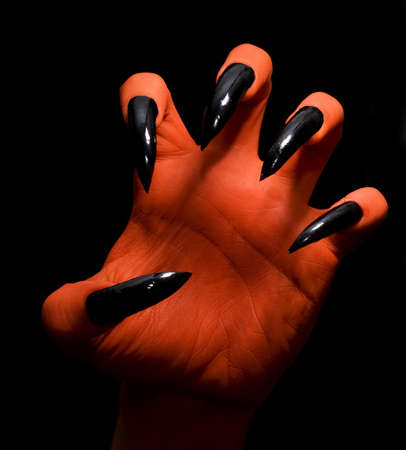 Red spooky devil hand on a dark background catching you