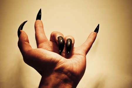 Demonic hand showing rock-music gesture. Colored vibrant image