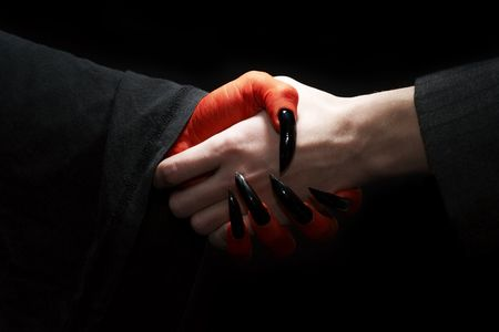 Economic conceptual image. Male businessman handshake with devil. Dark contrast lighting