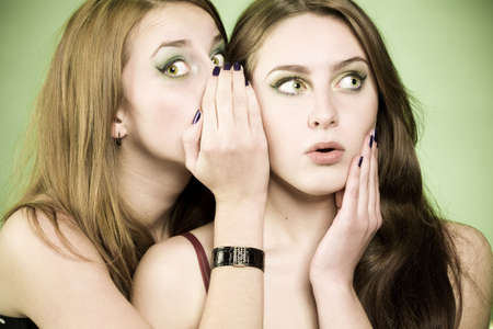 One girl whispering to other some news. Surprised face and palm near face in second girl. Image in green spring colors