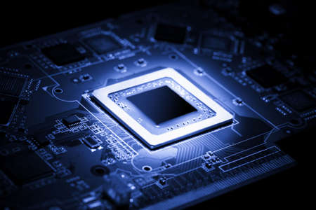 Glowing modern processor. Big illuminated graphic processor surrounding by other electrical components. Special tone image. Low aperture shot, focus on lower part of chip. Stock Photo