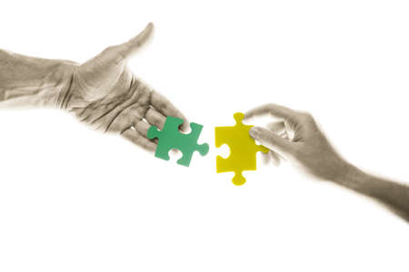 Female and male hands holding a pieces of puzzle on white background. Conceptual image: teamwork, partnership, working together. Two puzzles isolated with clipping paths. photo