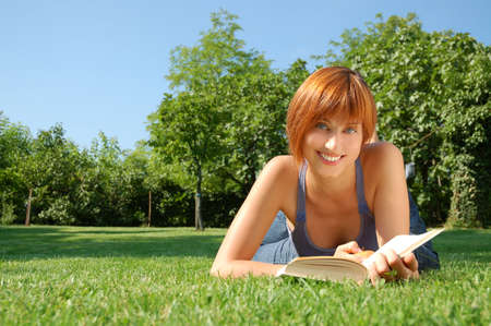 Girl lying in a meadow with apple and book photo