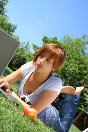 Girl lying in a meadow using a laptop photo