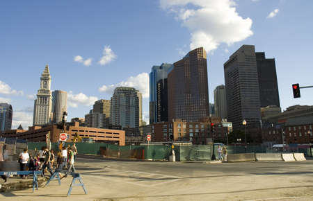 Lively Boston street in construction with clock tower and skylines behind photo