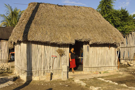 Yucatan Peninsula, Mexico - December 14th, 2005; Maya woman in front of a typical mayan house, - roof made with palm trees