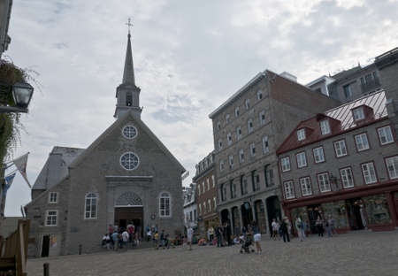 royale: Quebec, Canada - August 21th, 2009 : tourists visiting the old  church of Notre-Dame-des-Victoires in Place Royale of Quebec city downtown. Construction was started in 1687 .UNESCO World Heritage Site.