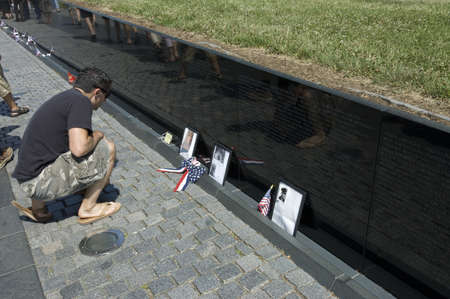Washington, DC, USA - June 24th, 2007 : young man kneeled  at  the wall of the Vietnam Memorial in the National Mall and Memorial Parks of Washington, DC, in front of relative killed during the war Stock Photo - 9638250