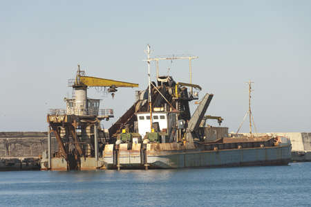 Chania, Greece - May 11th, 2007 : fishermen rusty boat with crane on harbor of Chania, Crete Island, Greece