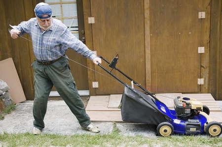 paysagiste: Québec, Canada - Juillet 2th, 2006: senior de départ d'une tondeuse manuelle, se concentrer sur l'outil - cinéma