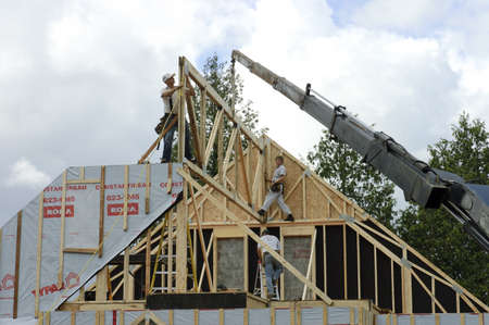Quebec, Canada - July 4th, 2006 : Construction worker framing the roof of a country house with help of a crane Stock Photo - 10368898