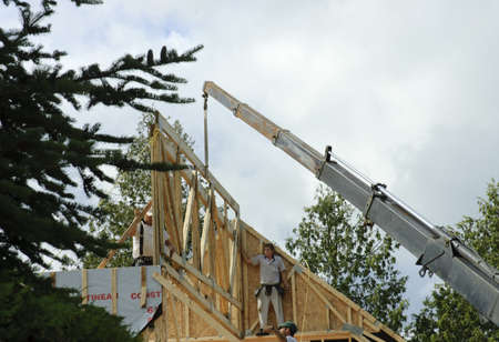 manoeuvre: Quebec, Canada - July 4th, 2006 : Construction worker framing the roof of a country house with help of a crane