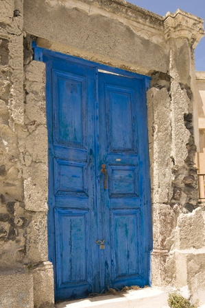 wooden grungy blue door painted and locked in Chania, Greece photo