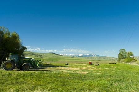 Montana, USA - May 17th, 2006 : Montana farmland with tractor and farm equipment  in the mountains of Montana state, USA