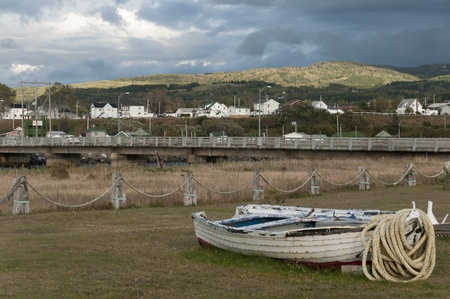 Quebec, Canada - September 18th, 2009 : abandoned fishing boat with rope and scenic view of village of Mont Ste-Anne, Quebec, Canada