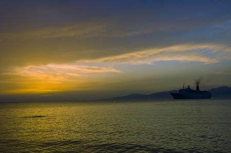 myconos: Myconos, Greece - May 7th, 2007   sunset on Aegean sea with cruise ship silhouette entering Myconos harbor at , Greece