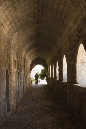 14th century: Rethymnon, Greece - May 11th, 2007 : Tourist under the arched alley of the Greek Orthodox Arkadi monastery, founded on 14th century AD,  Crete,  Greece