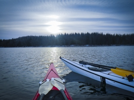 anchoring: kayaks anchored at sundown on sea in Black Cove, Nova Scotia coast, Canada Stock Photo