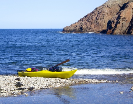 well equipped: kayak well equipped and ready for expedition,  anchored on a beach of  Cape Breton,, Nova Scotia, Canada Stock Photo
