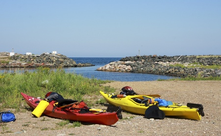 well equipped: kayaks well equipped and ready for expedition,  anchored on a beach of Pleasant Bay, Nova Scotia, Canada