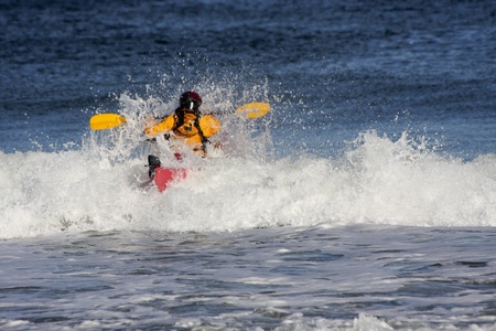 falling tide: Kayak surfer on the crest of a wave in rough sea of Nova Scotia coast, Canada Stock Photo