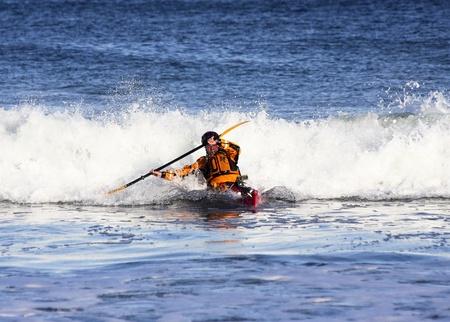 mare agitato: Kayak uomo che esce da grande onda sul mare agitato della costa Nova Scotia, Canada Archivio Fotografico