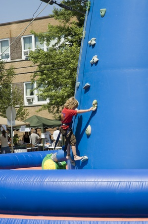 MONT LAURIER, QUEBEC, CANADA - JULY 13, 2006 : Little blondie girl training on an outdoor climbing tower at a fair show held in street of rural country of Quebec, Canada