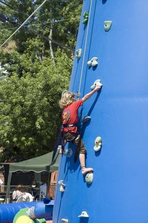 niño trepando: Mont Laurier, Quebec, Canadá - 13 de julio del 2006: Poco rubia niña de la formación en una torre de escalada al aire libre en un espectáculo de feria que se celebra en la calle del país rural de Quebec, Canadá Editorial