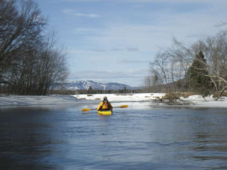 kayak surfer on an icy lake at the end of winter with view on Mont Tremblant peak in background, Quebec, Canada
