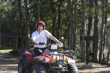 quad: young man riding a Quad in Quebec rural road, Canada Stock Photo