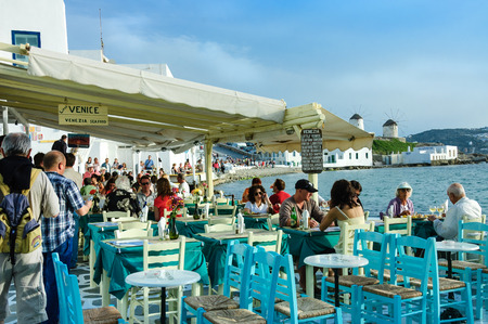 Myconos, Greece - May  7, 2007 : tourists at restaurant on the beach near the four famous windmills of Mykonos, Greece