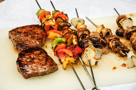 BBQ Steaks and vegetables ready to eat set over a white tablecloth