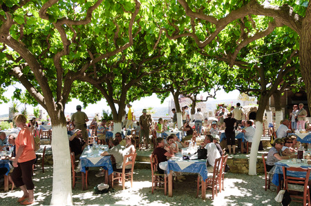 degustation: Crete, Greece - May 13, 2007 : tourists at a wine degustation on restaurant in front of Panagia orthodox church in Crete island