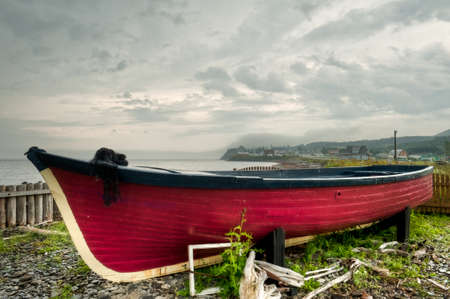muck: Old abandoned red boat on the beach of small village of  LAnse-au-Griffon in Gaspe Peninsula, Quebec, Canada