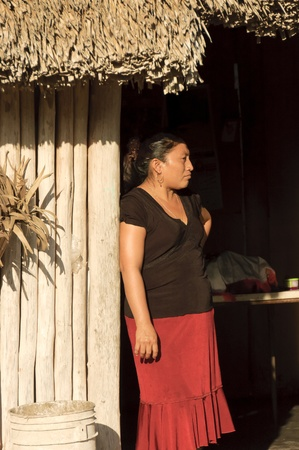 campesino: Yucat�n, M�xico - el 14 de diciembre de 2006;  Retrato de mujer maya en frente de su casa, pen�nsula de Yucat�n, M�xico - techo con palmeras
