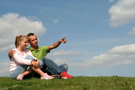 Couple sitting on grass and pointing Stock Photo - 460030
