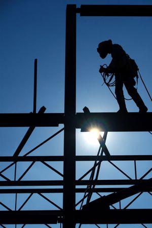 Welder walks a construction sites high steel