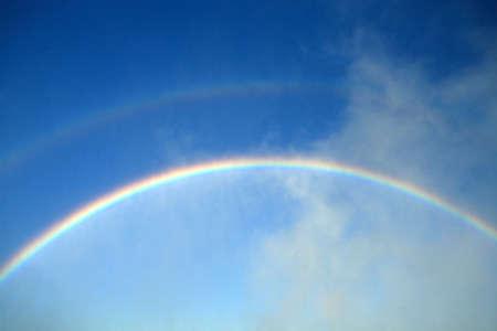 深い青色の空に対してプライマリおよびセカンダリの rainsbows。