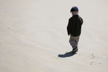 ponder: A little boy walking alone on the beach Stock Photo