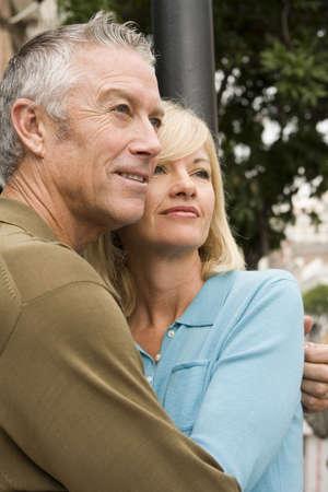 Older couple cuddling outside Stock Photo