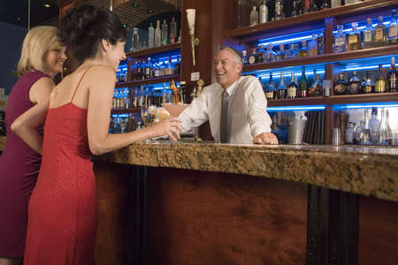 cousin: Two ladies talk to a bartender at the bar Stock Photo