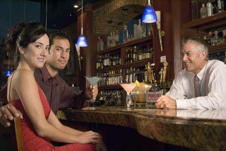 sidewalk talk: Two ladies talk to a bartender at the bar Stock Photo
