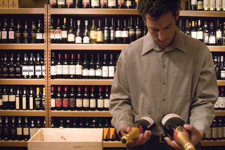 Man looking at wine bottles Stock Photo