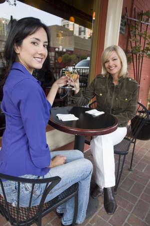 sidewalk talk: Two woman enjoying drinks outside