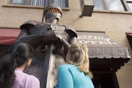 sidewalk talk: Two woman gazing at a large knight in armor