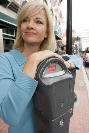 expired: Woman leaning on an expired parking meter Stock Photo