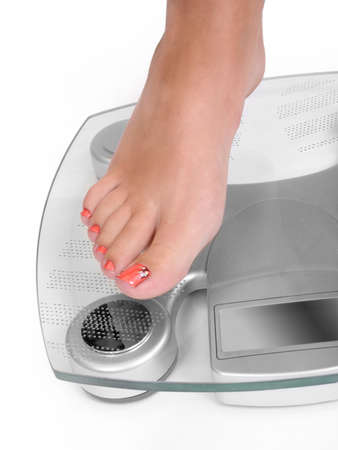 overeat: Foot on a bathroom scale - Isolated